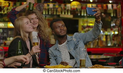 Group Of Young Friends Drinking And Laughing In A Bar. -...