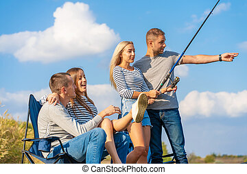 Group of young friends fishing on the pier by lakeside