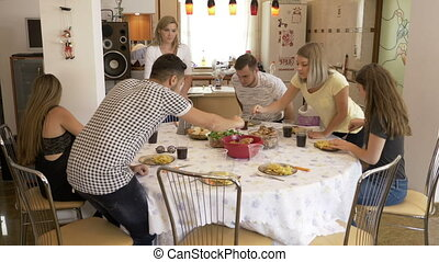 Group of young friends gathering in the dinning room having together a tasteful lunch meal leisure food and holiday concept