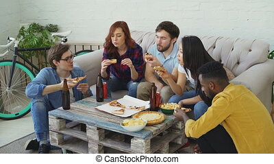 Group of young friends having home party and eating pizza taking it from table. Students talking and have fun indoors