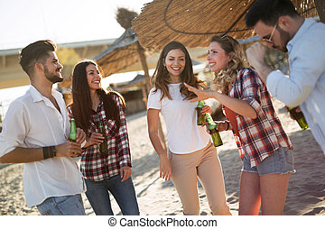 Group of young friends laughing and drinking beer