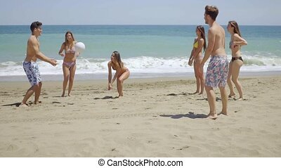 Group of young friends playing soccer on a beach