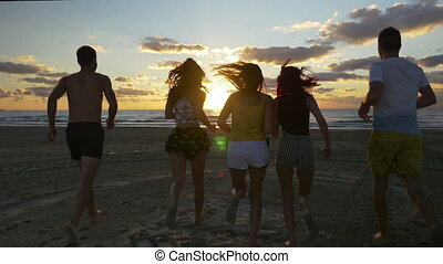 Group of young friends running into the water from the beach at sunset