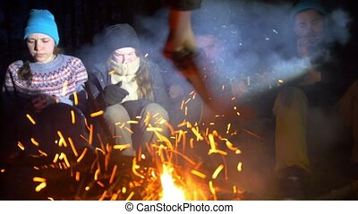 Group of young friends sitting at the bonfire and playing guitar in the evening wood