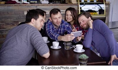 Group of young friends sitting at the restaurant together talking to each other and using digital gadget. Three handsome men and two smiling women looking at the screen of smartphone and smiling.