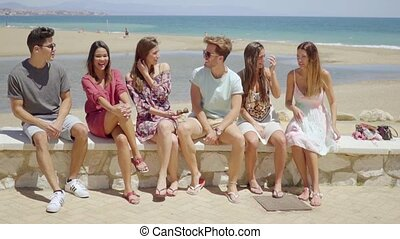 Group of young friends sitting on a seafront wall - Group of...