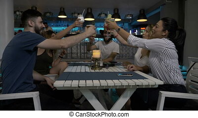 Group of young friends toasting drinks at the bar lounge celebrating clink glasses and having a great time