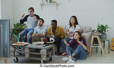 Group of young friends watching football game on TV together eating snacks and drinking beer at home. Men are happy with their team winning but girls disappointed