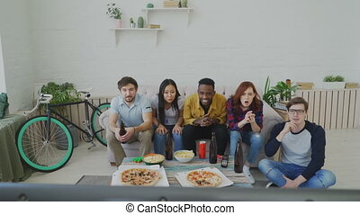 Group of young friends watching games match on TV together eating snacks and drinking beer. African man is happy about his team winning but others are disappointed
