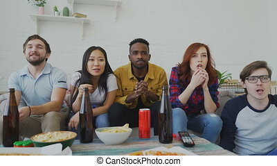 Group of young friends watching games match on TV together eating snacks and drinking beer. Some of them happy with their team winning but african man disappointed