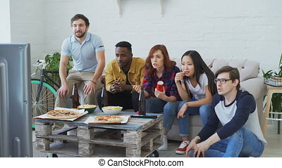 Group of young friends watching olympic games match on TV together eating snacks and drinking beer on holidays at home indoors. Some of them happy with their team winning but others disappointed