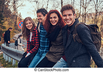 Group of young friends with backpacks sitting on guardrail near road with a beautiful forest and river in the background.