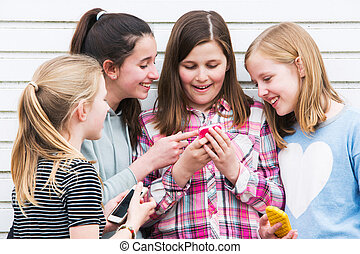 Group Of Young Girls Outdoors Looking At Message On Mobile Phone