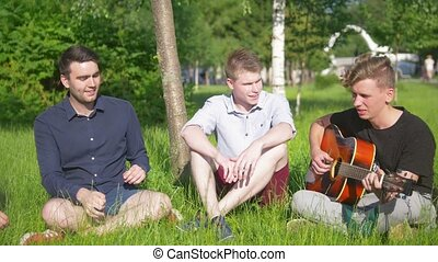 Group of young happy friends have a rest on the grass, young man playing the guitar