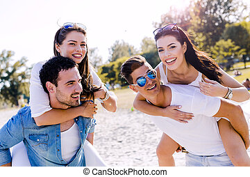 Group of young happy people carrying women on a sandy beach