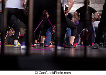 sporty women exercising with a rubber bands