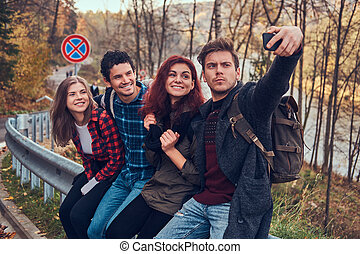 Group of young hikers with backpacks sitting on guardrail near road and doing selfie.