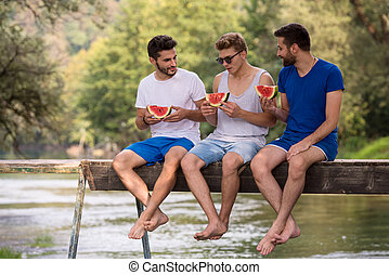 men enjoying watermelon while sitting on the wooden bridge