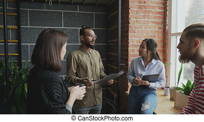 Group of young multi-ethnic students disscussing start-up project while standing together near window in modern office