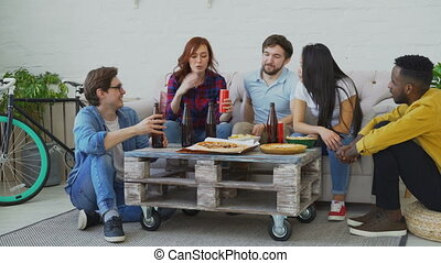 Group of young multiethnic friends talking together and have fun while having home party enjoying snacks and beer
