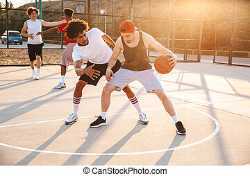 Group of young multiethnic men basketball players playing ...