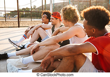 Group of young multiethnic men basketball players resting at...