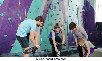Group of young people and child are putting on safety harnesses in climbing center getting ready for extreme entertainment. People and sports concept.