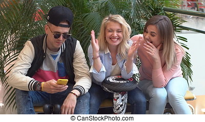 Group of young people are sitting on a bench in a shopping center. Teenagers in the mall.