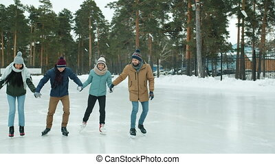 Group of young people Asian and Caucasian ice-skating in park laughing having fun
