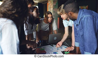 Group of young people colleagues is discussing charts and graphs standing around table in modern office. Business, teamwork and professionals concept.