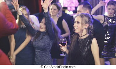 Group Of Young People dancing at Party in night club