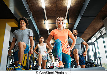 Group of young people doing exercises in gym