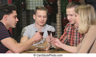 Group of young people drinks off liquor at the restaurant