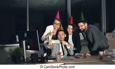 Group of young people is making online video call skyping from office wearing party hats talking, waving hand, sending air kisses and showing thumbs-up.