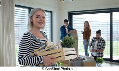 Group of cheerful young people moving in new home, house sharing concept.