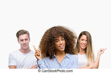 Group of young people over white background very happy pointing with hand and finger to the side