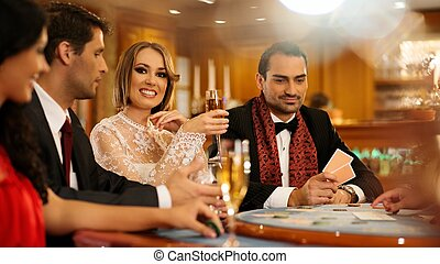 Group of young people playing poker in a casino