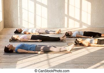 group of people lying on mats doing balasana yoga asana