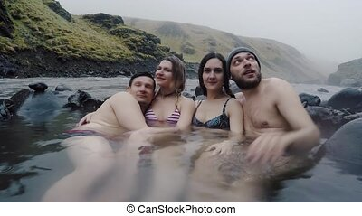 Group of young people relaxing on hot springs in mountains...