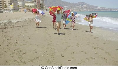 Group of young people running along a resort beach trailing...