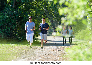 group of young people running in park