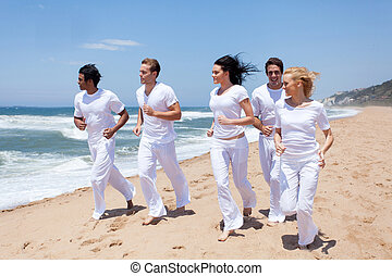 group of young people running on the beach
