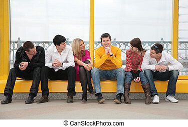 group of young people sit on footbridge