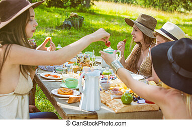 Group of young people sitting at a brunch in the countryside