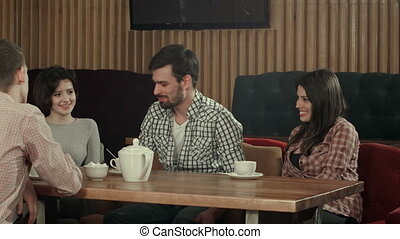 Group of young people sitting at a cafe, talking and enjoying