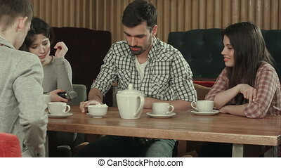 Group of young people sitting at a cafe, talking and drinking tea
