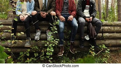 Group of young people sitting on logs