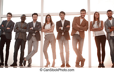 group of young people standing in an office with a large window