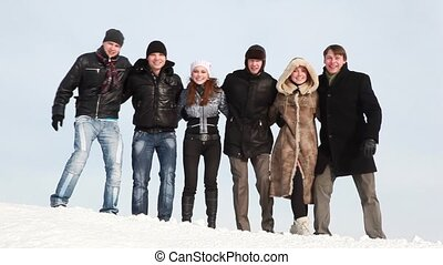 Group of young people start sway on slope with snow in winter