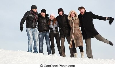 Group of young people start sway on slope with snow